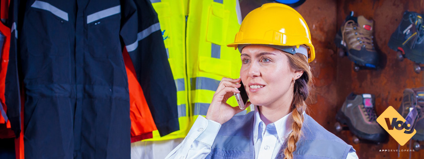 Construction woman using her mobile phone to work on the go using mobile applications developed in Canada